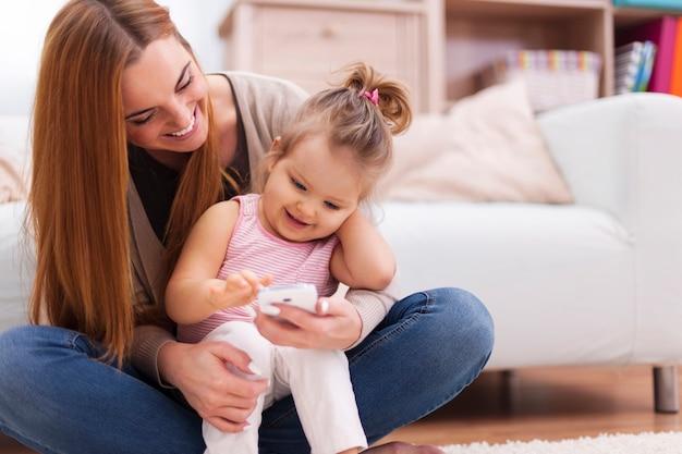 Glückliche familie mit zeitgemäßem handy zu hause