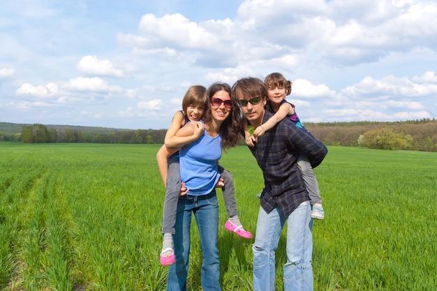 Glückliche familie mit zwei kindern auf der grünen wiese