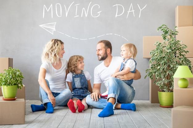 Glückliche familie mit zwei kindern, die in neues zuhause spielen
