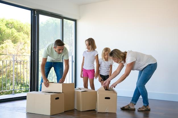 Glückliche familie mit zwei kindern, die kisten im neuen zuhause auspacken