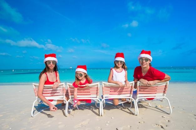 Glückliche familie mit zwei kindern in santa hat in den sommerferien