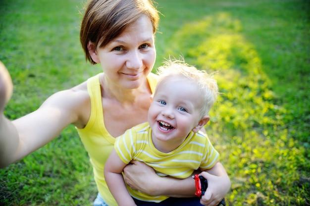 Glückliche familie: mittelalterfrau und ihr entzückender kleinkindenkel am park, der selfie macht