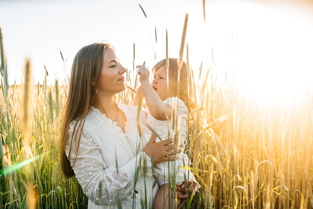 Glückliche familie, mutter in einem kleid mit einem süßen kleinen baby auf einem goldenen weizenfeld bei sonnenuntergang. sommertag.