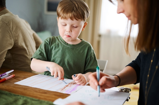 Glückliche familie. mutter mit dem kleinen sohn, der zusammen malt und zeichnet. kaukasischer junge mit seiner mutter, die zu hause studiert