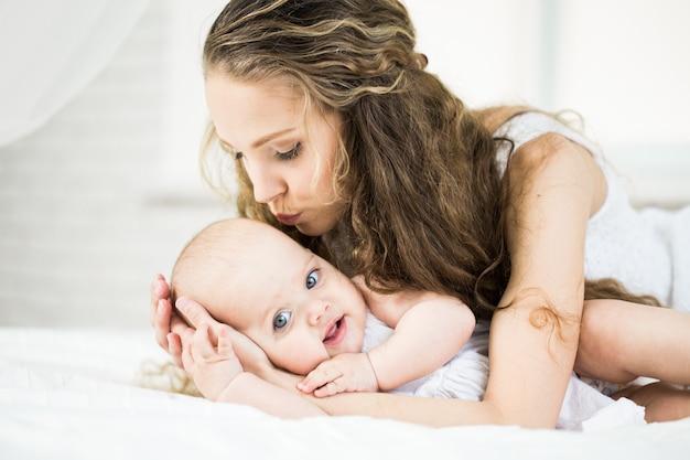Glückliche familie. mutter spielt mit ihrem baby im schlafzimmer.