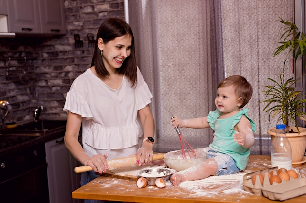 Glückliche familie, mutter, tochter spielen und kochen in der küche, kneten den teig und backen kekse