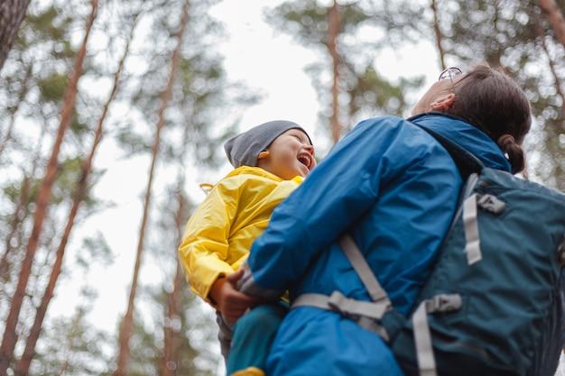 Glückliche familie mutter und kind gehen im wald nach dem regen in regenmänteln zusammen, umarmen und schauen in den himmel