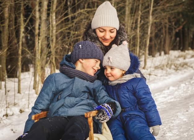 Glückliche familie mutter und kinder im winter auf einem spaziergang. liebe mama und kinder