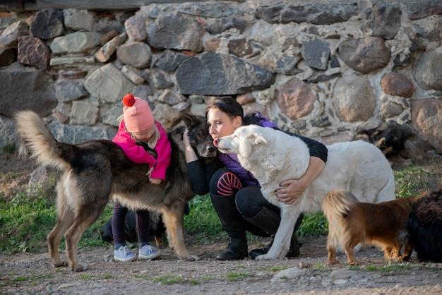 Glückliche familie mutter und mädchen tochter, die spaß mit vielen hunden im freien haben