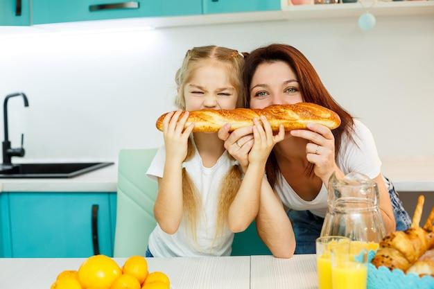 Glückliche familie, mutter und tochter essen ein brot, das von verschiedenen seiten beißt. familienbeziehungen des kindes mit den eltern