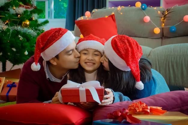 Glückliche familie. mutter und vater küssen tochter im wohnzimmer zu hause im weihnachtsfeiertag