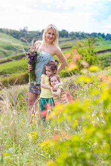 Glückliche familie - mutter und zwei töchter mit lächelnden gesichtern im freien
