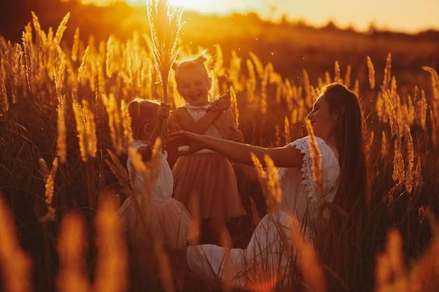 Glückliche familie, mutter und zwei töchter. mutter spielt mit ihrer tochter auf der straße im park bei sonnenuntergang.