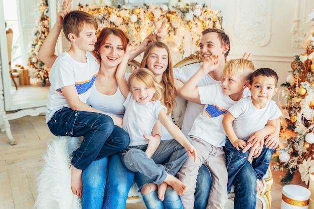 Glückliche familie mutter vater fünf kinder entspannen sich spielen in der nähe von weihnachtsbaum