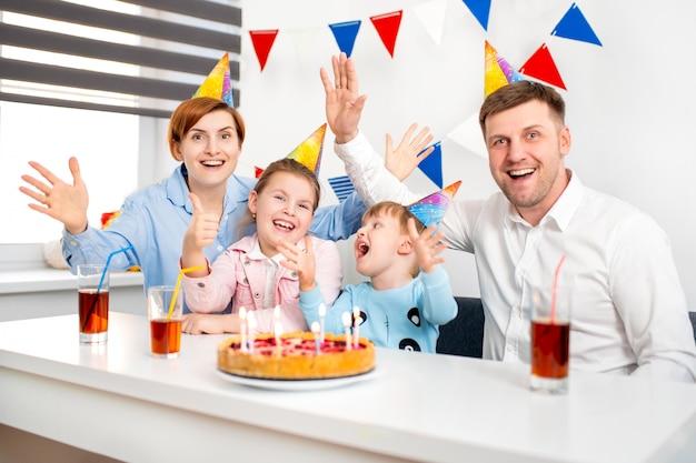 Glückliche familie, mutter, vater, sohn, tochter, die eine kindergeburtstagsfeier mit dem kuchen feiern.