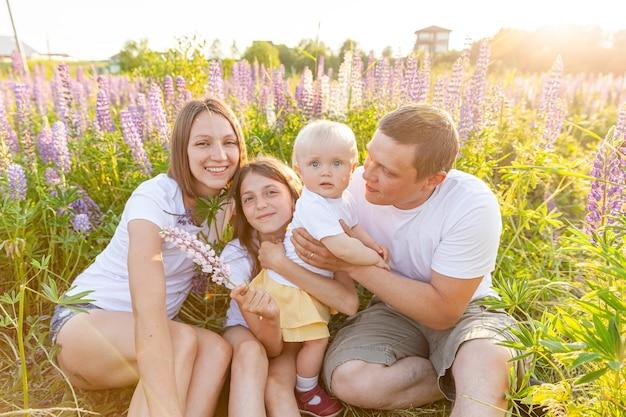 Glückliche familie mutter vater umarmt kinder im freien. mama papa und töchter spielen auf der wiese im freien