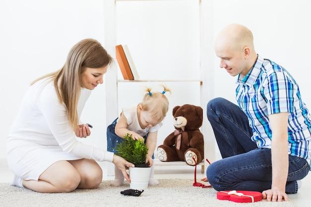 Glückliche familie, mutter, vater und ihr baby spielen zusammen im wohnzimmer zu hause.