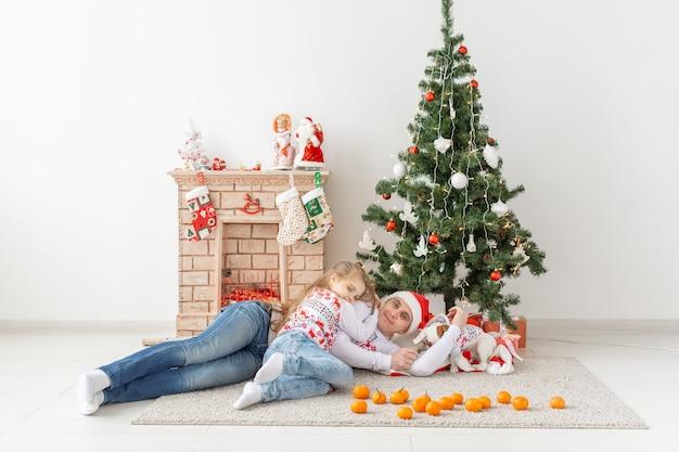 Glückliche familie mutter vater und kind am weihnachtsbaum zu hause.