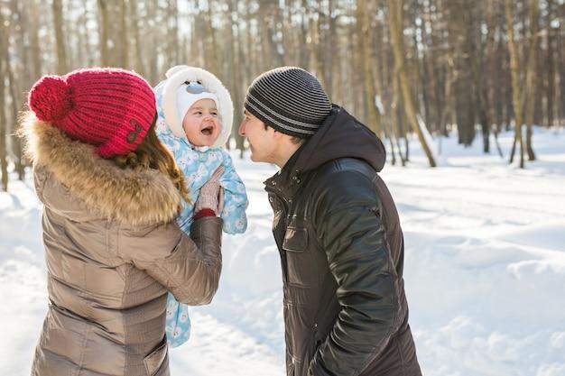 Glückliche familie. mutter, vater und kind auf einem winterspaziergang.