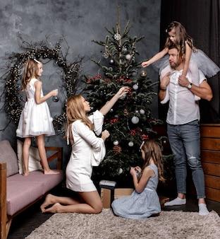 Glückliche familie mutter, vater und kinder töchter schmücken weihnachtsbaum im wohnzimmer interieur zu hause.