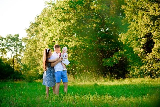 Glückliche familie: muttervater und kindertochter im park bei sonnenuntergang.
