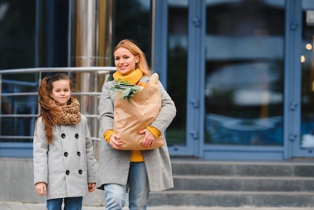 Glückliche familie nach dem einkaufen mit einkaufstüten auf dem parkplatz nahe einkaufszentrum. mutter mit tochter.