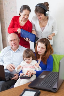 Glückliche familie nutzt verschiedene elektronische geräte im haus