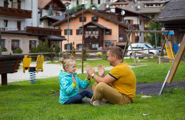 Glückliche familie. papa mit tochter sitzt auf einer wiese in einem park in canazei, italien