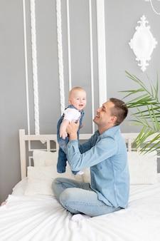Glückliche familie, papa spielt mit baby zu hause auf dem bettkonzept oder glückliche vaterschaft