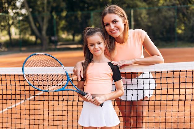 Glückliche familie posiert gut auf dem tennisplatz
