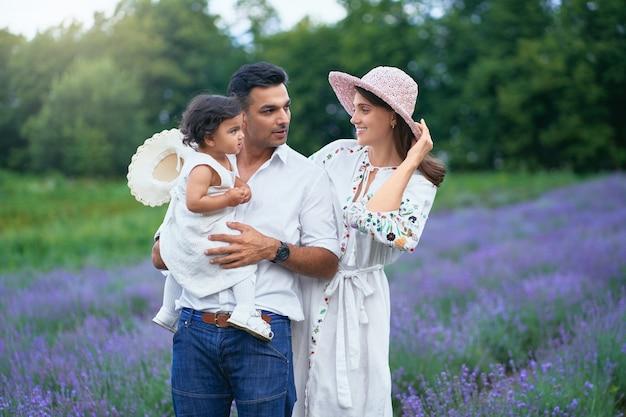 Glückliche familie posiert im lavendelfeld