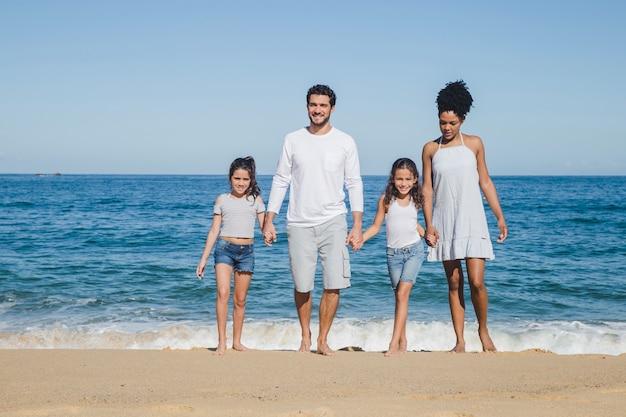 Glückliche familie posiert und händchen haltend