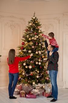 Glückliche familie schmücken den weihnachtsbaum drinnen zusammen. liebevolle familie. frohe weihnachten und schöne feiertage