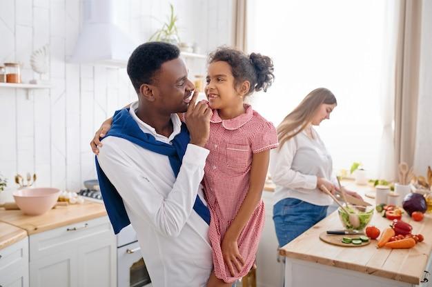 Glückliche familie, schönes frühstück in der küche. mutter, vater und ihre tochter kochen morgens, gute beziehung
