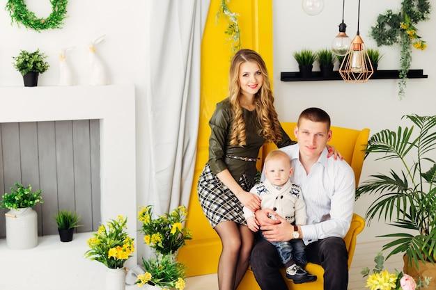 Glückliche familie sitzt auf einem schicken gelben sessel, um sie herum ein kamin, blumentöpfe, gelbe türen mit einem vorhang