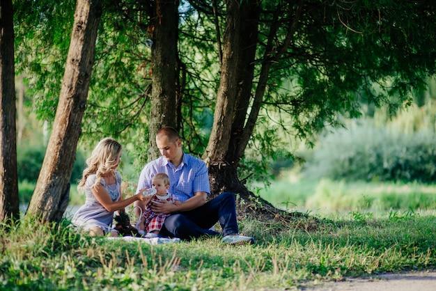 Glückliche familie spazieren im grünen sommerpark. picknick