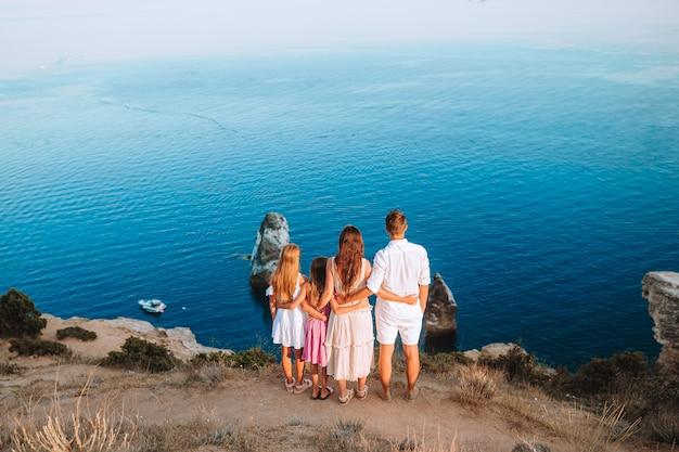 Glückliche familie steht gegen bergsonnenuntergang. reisetourismus abenteuer konzept
