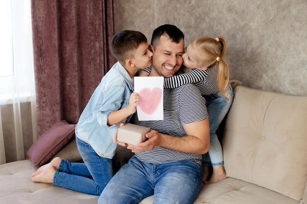 Glückliche familie, tochter und sohn geben dem vater ein geschenk und eine karte für den urlaub.