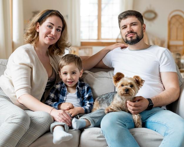 Glückliche familie und hund bleiben drinnen