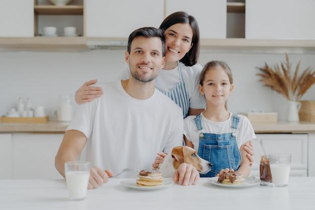 Glückliche familie und hund posieren in gemütlicher küche, essen frische hausgemachte pfannkuchen mit schokolade und milch, schauen positiv in die kamera. mutter im schurz umarmt ehemann und tochter, kocht gern für sie