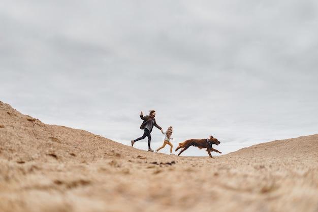 Glückliche familie und ihr hund laufen am sandstrand entlang. mutter und sohn spielen mit einem hund auf der straße