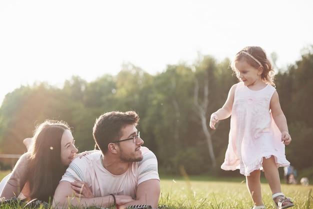 Glückliche familie, vater der mutter und tochter des babys in der natur bei sonnenuntergang