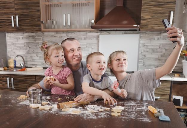 Glückliche familie vater mama und zwei kinder machen selfies in der küche, während sie kekse machen. zusammen kochen glückliche familiäre beziehungen