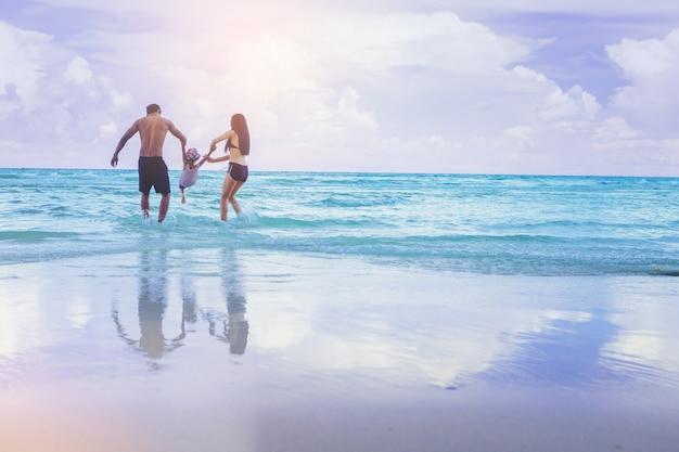 Glückliche familie, vater, mutter und kind haben spaß am strand ins meer laufen.