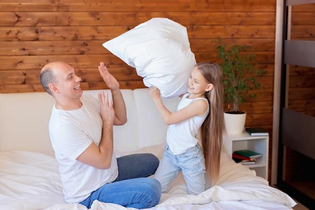 Glückliche familie, vater und tochter lachen, spielen, kämpfen mit kissen und springen im schlafzimmer ins bett.