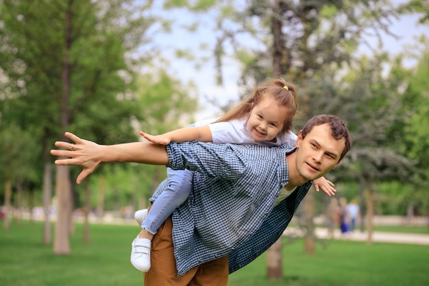 Glückliche familie, vater und tochter spielen im sommerpark