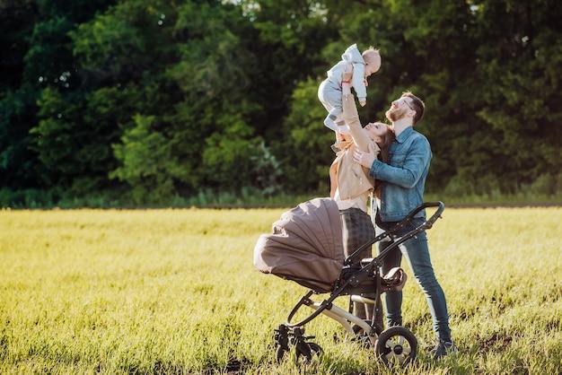 Glückliche familie verbringt zeit im freien. mutter hält baby in ihren armen und hebt es hoch
