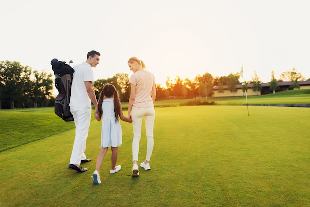 Glückliche familie verlässt das golffeld nach dem spiel.