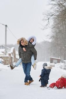 Glückliche familie viel spaß draußen in der nähe des hauses im winter. glückliches familien- und urlaubskonzept