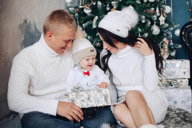 Glückliche familie von drei posen für das weihnachtsfamilienfoto nahe dem weihnachtsbaum